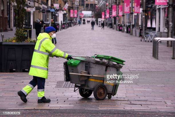 A street cleaner wearing a face mask is seen in Glasgow on March 24 2020 after Britain ordered a lockdown to slow the spread of the novel coronavirus...