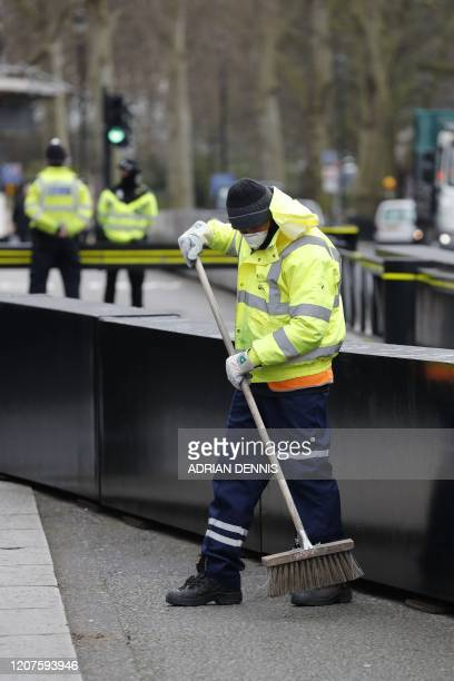 A street cleaner wearing a mask works outside the Houses of Parliament in London on March 18 2020 amid the coronavirus outbreak The British...