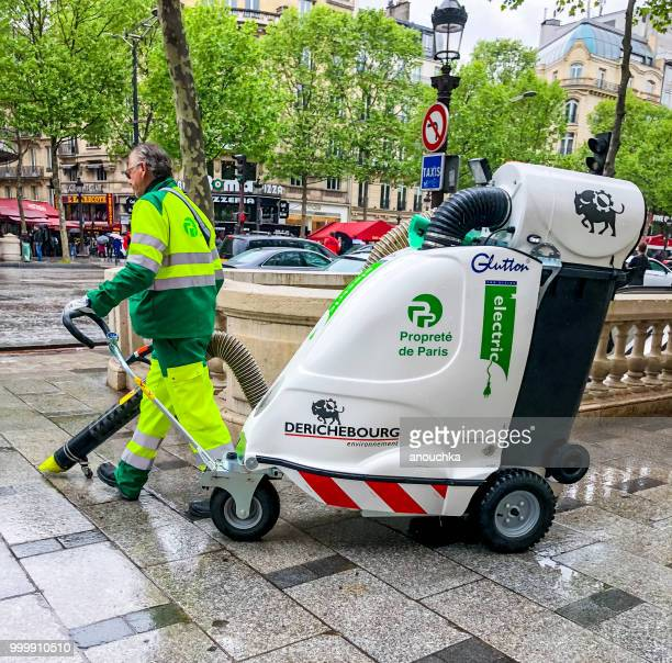 street cleaner working on avenue des champs-elysees. - street sweeper stock pictures, royalty-free photos & images