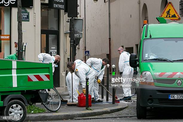 Street cleaners clean up the sidewalks around the 'Bataclan' concert hall on November 16, 2015 in Paris, France. A Europe-wide one-minute silence was...