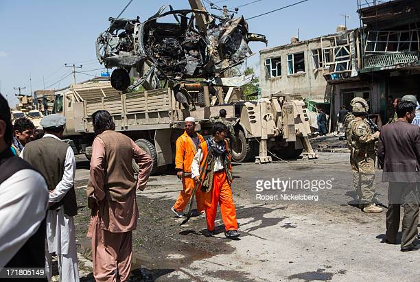 Street cleaners walk by as Afghan security personnel remove an American-made SUV destroyed by a suicide car bomber May 16, 2013 in Kabul,...