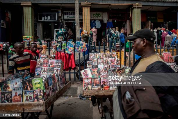 Street clothing seller passes by two movie vendor stands at Idumota market in Lagos on February 19, 2019. - With its turncoats, crimes, cash and even...