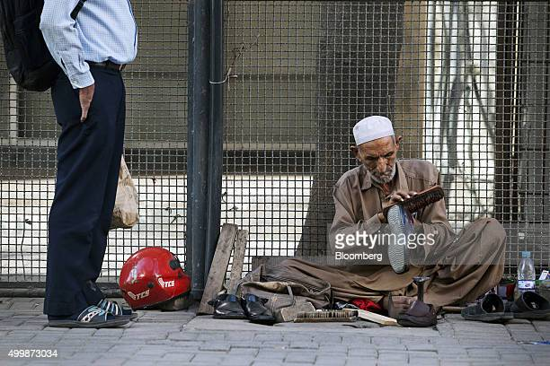 A street cobbler cleans a shoe for a customer on a pavement in Karachi Pakistan on Wednesday Dec 2 2015 A committee of Pakistan's top economic minds...