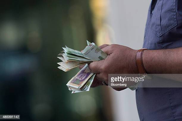 A street currency trader counts out rial banknotes in Tehran Iran on Wednesday Aug 26 2015 The nuclear agreement between Iran and global powers has...