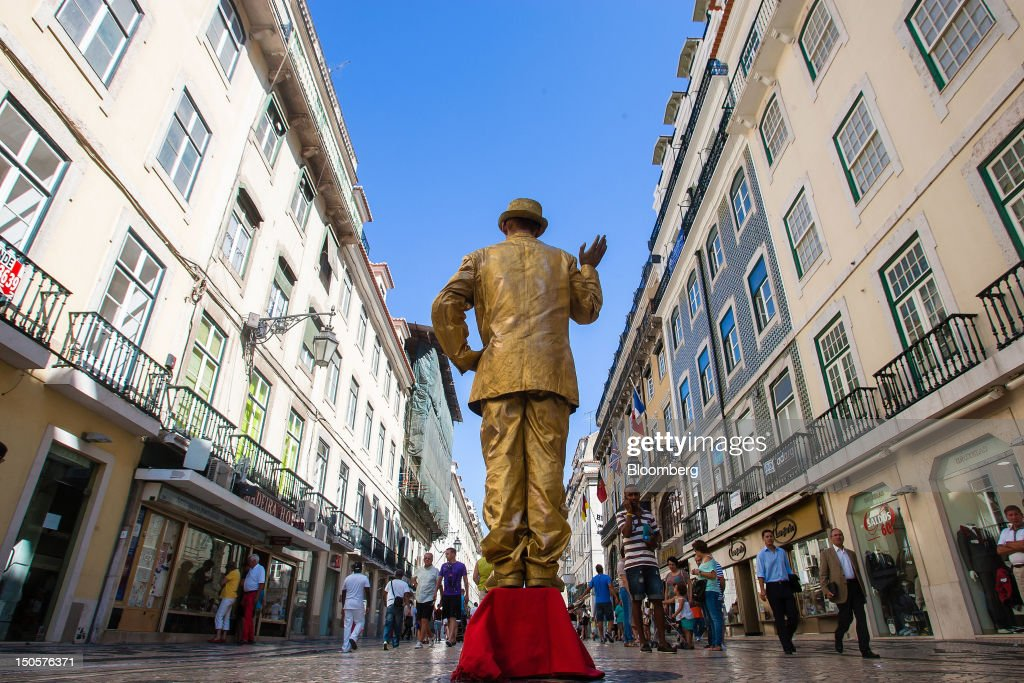 A street entertainer covered in gold performs for pedestrians on a shopping street in Lisbon, Portugal, on Wednesday, Aug. 22, 2012. In Portugal, the historical home of some of Europe's biggest gold reserves, the number of jewelry stores, which include cash-for-gold shops, increased 29 percent in 2011 from a year earlier, a study commissioned by parliament found. Photographer: Mario Proenca/Bloomberg via Getty Images