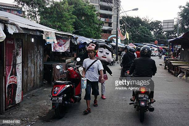 Street entertainers dressed as dolls are seen at the Slum area in Jakarta Indonesia on July 11 2016 Indonesia is the most populous country in...