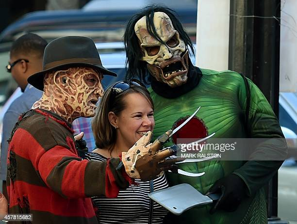 Street entertainers dressed as movie characters pose for photos with tourists on Hollywood Boulevard in Hollywood California on October 24 2014 A...