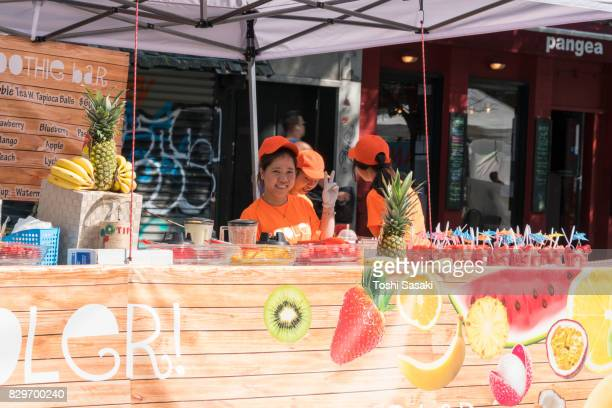 street fair was opened on the 2nd avenue at east village manhattan new york on jul. 16 2017. women sell fresh fruits juice at stand. - jul photos et images de collection