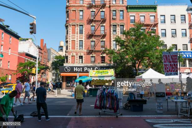 street fair was opened on the 2nd avenue at east village manhattan new york on jul. 16 2017. people walks down the 2nd avenue among the many street shops along the street. evening sunlight makes shadow on the avenue. - jul photos et images de collection