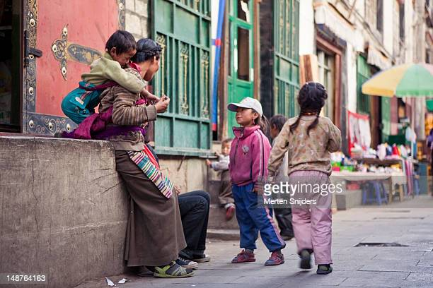 street family with several kids in an alley at barkhor square. - merten snijders stockfoto's en -beelden
