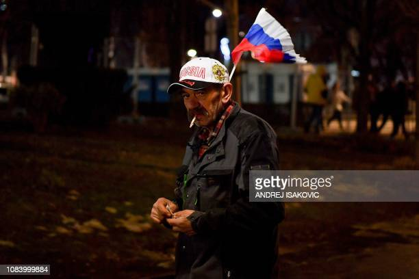 A street flags vendor counts his earnings as supporters of Serbian President and Russian President wait for their arrival in front of Belgrade's...