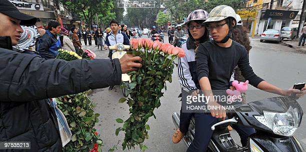 A street flower vendor shows off a bunch of roses to a young couple in hope of a sale on International Women's Day in downtown Hanoi on March 8 2010...