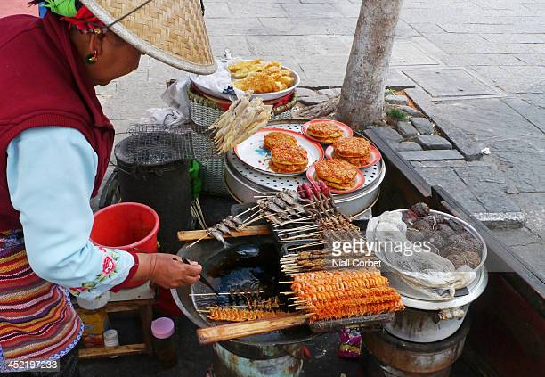 Street food stall selling a variety of delicious snacks including deep-fried skewers of shrimps, locusts, dragonfly nymphs and tiny fish, fried...