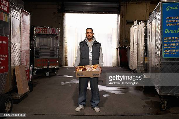 Street food vendor holding box of pastries in warehouse, portrait