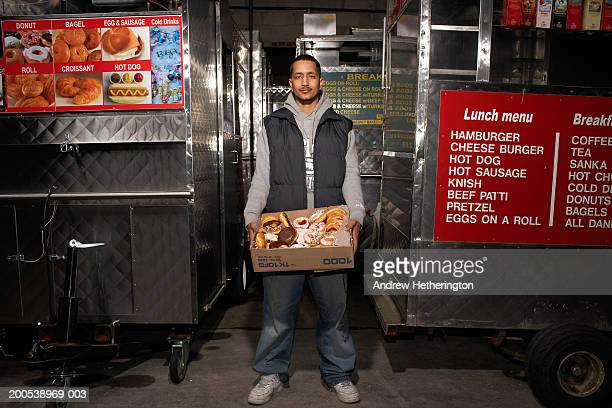 Street food vendor in warehouse holding box of pastries