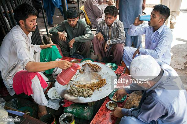 A street food vendor prepares an offalbased dish known as katakat at a roadside stall in Karachi Pakistan on Thursday May 28 2015 Pakistan's budget...