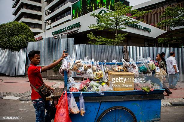 A street food vendor walks past a Starbucks coffee shop close to where the bombings happened remain closed for investigation on January 15 2016 in...