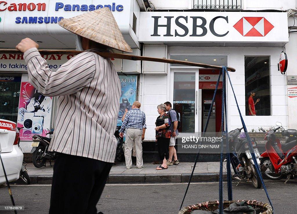 A street food vendor walks past an HSBC : News Photo