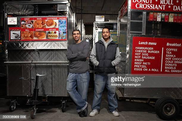 Street food vendors beside carts, portrait