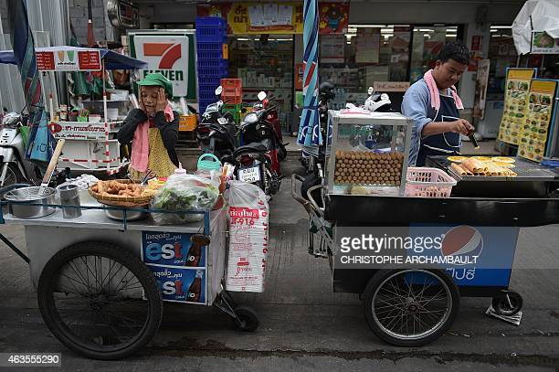 Street food vendors wait for customers in Bangkok on February 16 2015 Thailand's economy slowed sharply in 2014 to grow at its slowest pace for three...