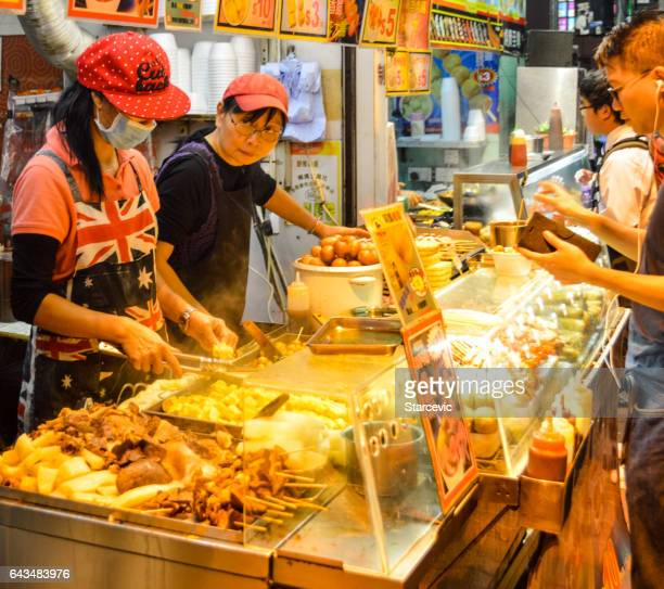 Street food vendors working in market stall