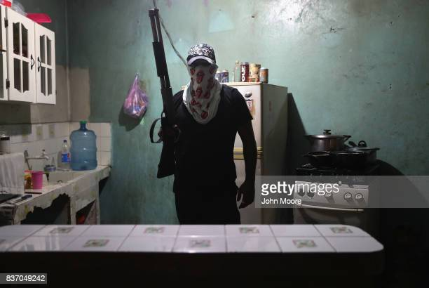 A street gang member poses for a photo in a safehouse on August 17 2017 in San Pedro Sula Honduras Rival gangs including MS13 and Barrio 17 tightly...
