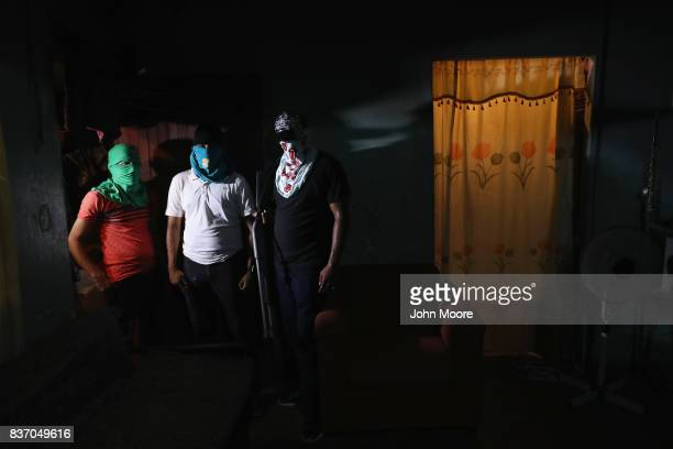 Street gang members pose for a photo in a safehouse on August 17 2017 in San Pedro Sula Honduras Rival gangs including MS13 and Barrio 17 tightly...