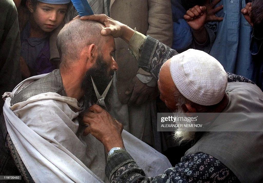 Street hairdresser cuts a  man's beard 1 : News Photo