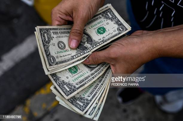 A street hawker counts dollar bills in a street of Caracas on November 19 2019 Venezuela's President Nicolas Maduro has been forced to loosen...