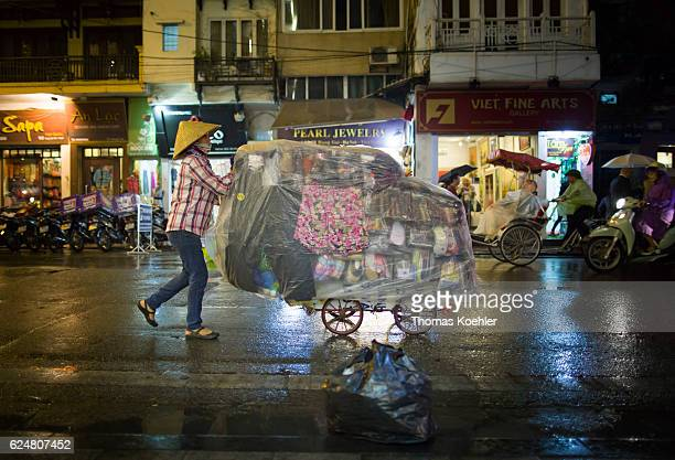 A street hawker pushes her sales van through the rainy Hanoi at the evening on October 30 2016 in Hanoi Vietnam