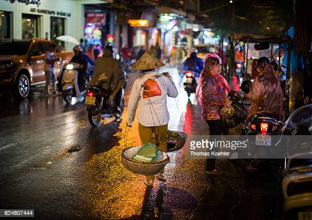 A street hawker runs with a carrying basket through Hanoi in the evening on October 30 2016 in Hanoi Vietnam