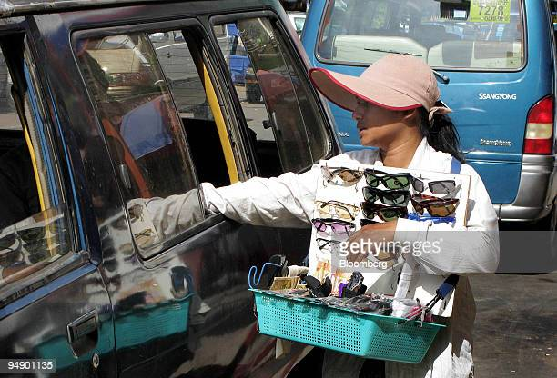 A street hawker tries to sell sunglasses to a customer through a car window on the streets of Phnom Penh Cambodia on Friday Aug 22 2008 Cambodia's...