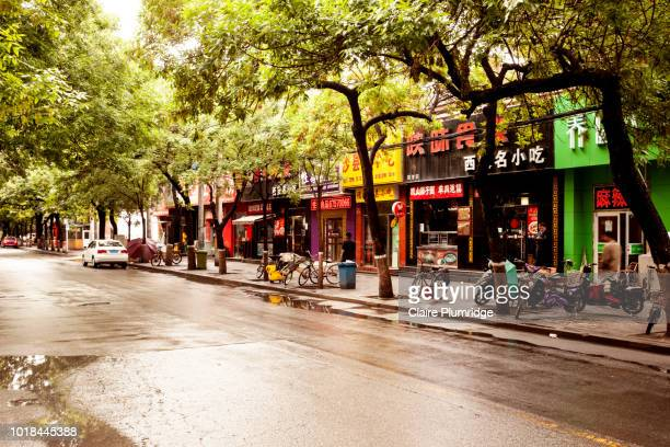 street in beijing, china, showing scooters and bicycles parked on the pavement. - claire plumridge stock pictures, royalty-free photos & images