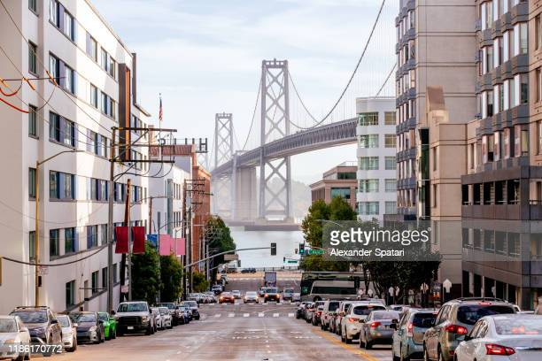 street in downtown of san francisco with san francisco-oakland bay bridge in the center, california, usa - san francisco california stock pictures, royalty-free photos & images
