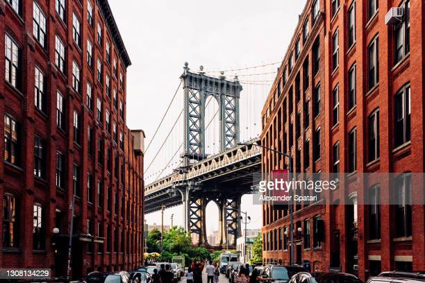 street in dumbo brooklyn with manhattan bridge between buildings, new york, usa - manhattan new york city stock pictures, royalty-free photos & images