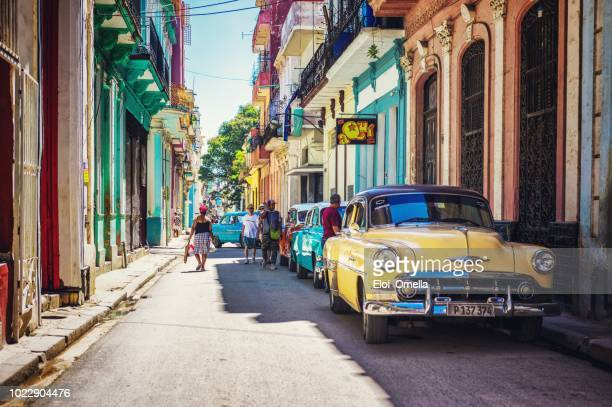 street in havana, cuba with coloured vintage american car - cuba stock pictures, royalty-free photos & images