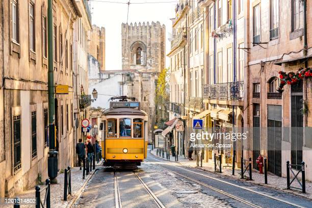 street in lisbon old town with yellow tram and lisbon cathedral in background, lisbon, portugal - provincie lissabon stockfoto's en -beelden