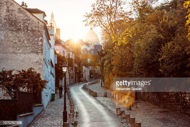 street in montmartre with dome of sacre coeur basilica during autumn, paris, france - morning photos et images de collection
