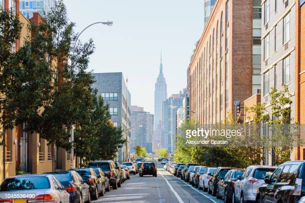 street in queens and empire state building in the center, new york city, usa - queens new york city stock pictures, royalty-free photos & images