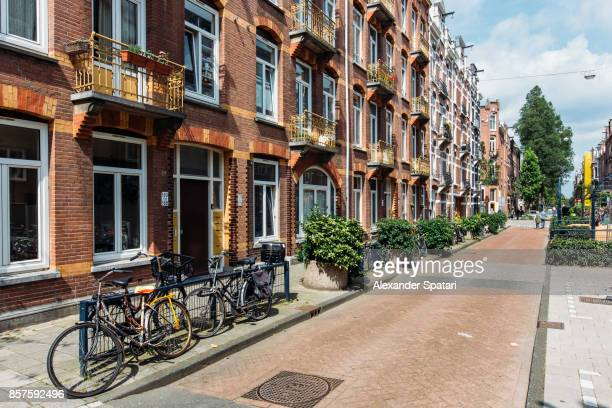 street in residential district in amsterdam, netherlands - stadtviertel stock-fotos und bilder