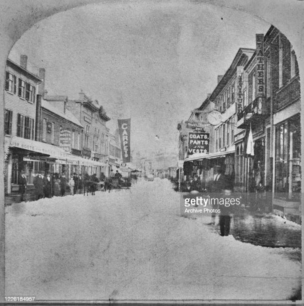 A street in Salem Massachusetts lined with shops selling carpets boots and shoes and coats pants and vests circa 1860 A stereoscopic image from...