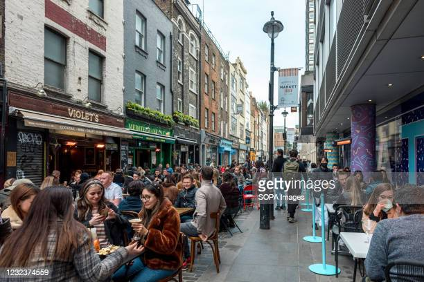 Street in Soho, London, with both sides packed with diners eating out as restaurants re-open after the COVID lockdown measures imposed by the UK...