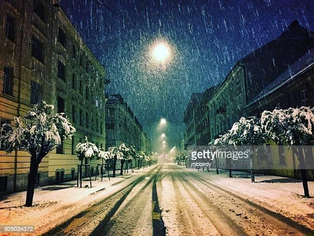 Street in spring by night in heavy snowing