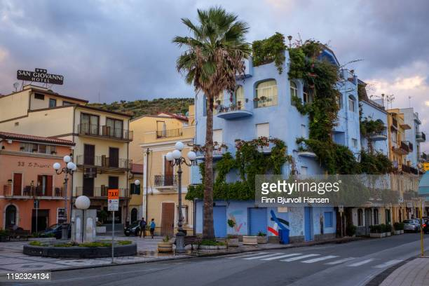 street in the town of giardini naxos, colorful bulidings and palmtree - finn bjurvoll stock pictures, royalty-free photos & images