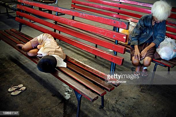 A street kid and a homeless old woman are sleeping at a bus station Poverty is huge in the Philippines and is a major factor in forcing young women...