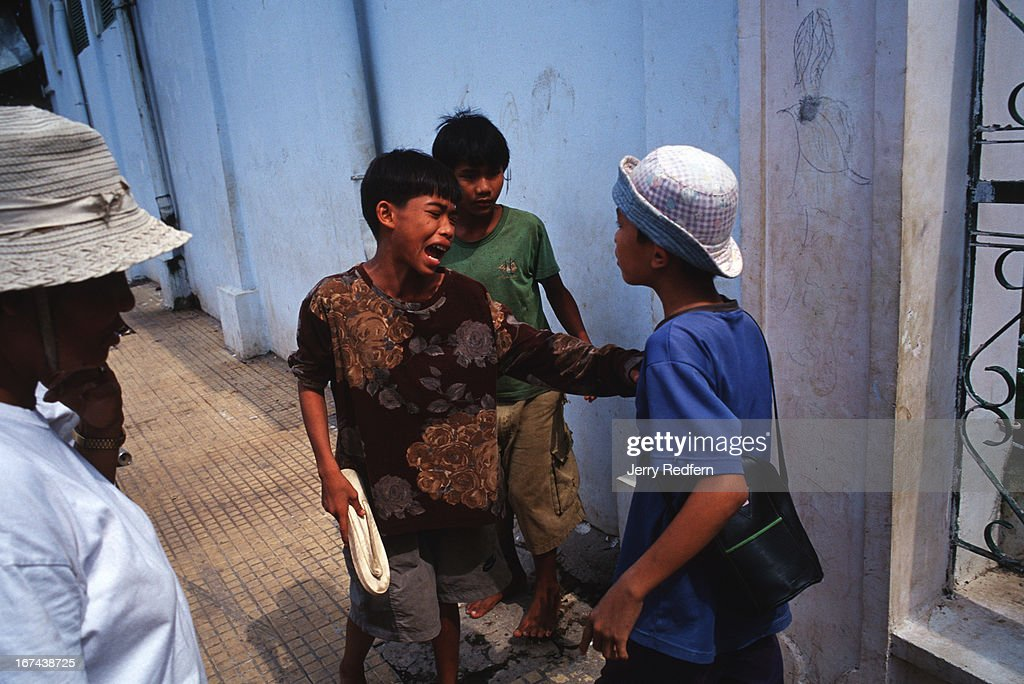 Street kids high from sniffing glue get in a scuffle while trying to play a game on the streets of Phnom Penh as a Khmer adult steps in to break them up. They were too high to remember what they were doing, leading to the fight..