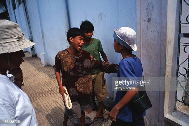 Street kids high from sniffing glue get in a scuffle while trying to play a game on the streets of Phnom Penh as a Khmer adult steps in to break them...