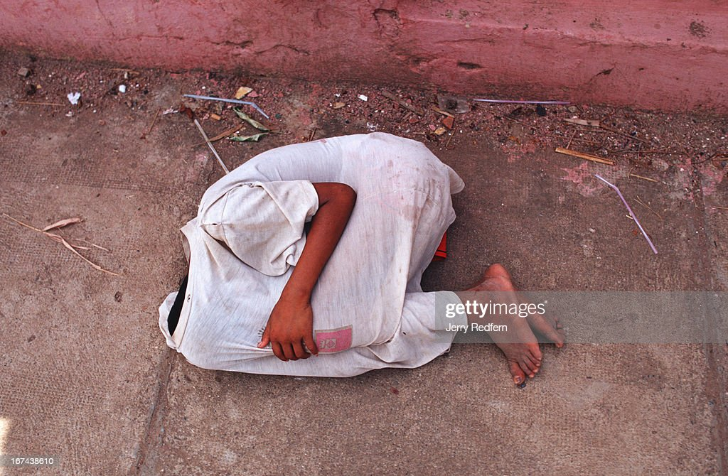 A street kids lies on the sidewalk taking a nap in the...