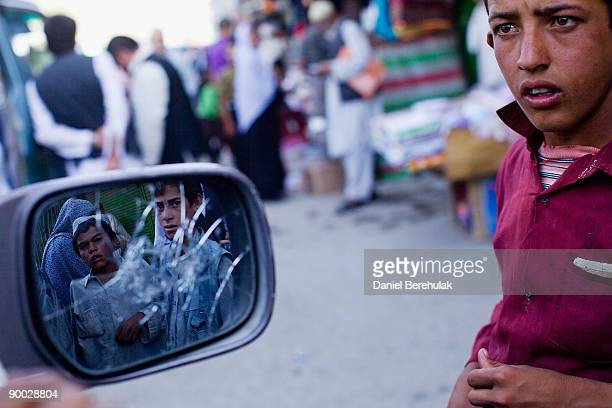 Street kids look on in a market place at at an election rally on August 14 2009 in Kabul Afghanistan The incumbent president Karzai is considered to...