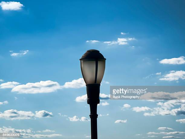 Street lamp against a clear sky with clouds